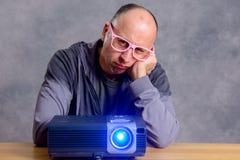 Hombre joven con la película aburrida del reloj del projektor Imagenes de archivo