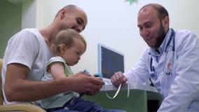 Hombre joven con la pequeña hija en la recepción del pediatra almacen de metraje de vídeo