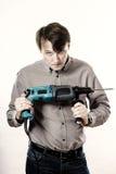 Hombre joven con la perforadora eléctrica aislada en blanco Foto de archivo