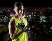 Hombre joven con la pesa de gimnasia que dobla el bíceps Fotografía de archivo