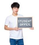 Hombre joven con la pizarra que muestra las frases de la oferta del estudiante Imagen de archivo libre de regalías