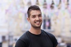 Hombre joven con la sonrisa en la calle Imágenes de archivo libres de regalías