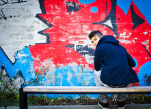 Hombre joven con la sudadera con capucha que se sienta en banco delante de la pintada Foto de archivo libre de regalías