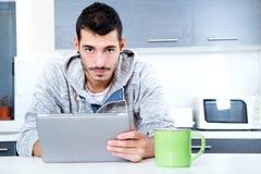 Hombre joven con la tableta en la cocina Imagenes de archivo