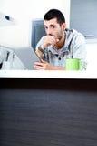 Hombre joven con la tableta en la cocina Imagen de archivo
