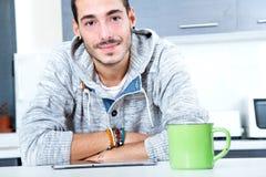 Hombre joven con la tableta en la cocina Fotografía de archivo