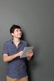 Hombre joven con la tableta que mira para arriba para copiar el espacio Imagenes de archivo