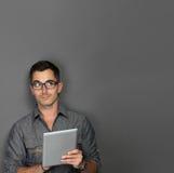 Hombre joven con la tableta que mira para arriba para copiar el espacio Imágenes de archivo libres de regalías