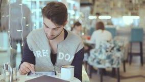 Hombre joven con la tableta que se sienta en café almacen de video