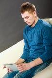 Hombre joven con la tableta que se sienta en el sofá en casa Fotos de archivo