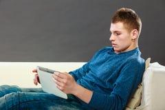 Hombre joven con la tableta que se sienta en el sofá en casa Imágenes de archivo libres de regalías