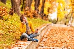 Hombre joven con la tableta y el hablar en el teléfono en al aire libre foto de archivo libre de regalías