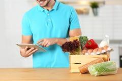 Hombre joven con la tableta y productos en cocina foto de archivo