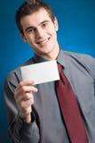 Hombre joven con la tarjeta de visita en blanco Foto de archivo libre de regalías