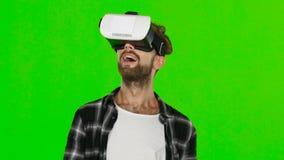 Hombre joven con las auriculares de la realidad virtual de VR en su cabeza Pantalla verde Cierre para arriba metrajes