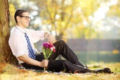 Hombre joven con las flores - contar con alguien Fotografía de archivo libre de regalías