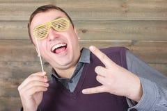 Hombre joven con las gafas de sol divertidas del inconformista en un palillo Imagen de archivo libre de regalías