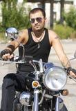 Hombre joven con las gafas de sol en una motocicleta Foto de archivo libre de regalías