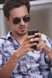 Hombre joven con las gafas de sol y el retrato al aire libre del smartphone foto de archivo