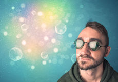 Hombre joven con las gafas de sol y las luces coloridas del bokeh Fotos de archivo libres de regalías
