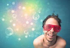Hombre joven con las gafas de sol y las luces coloridas del bokeh Fotografía de archivo