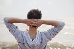 Hombre joven con las manos detrás de la cabeza, mirando hacia fuera al mar Fotos de archivo