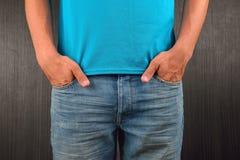 Hombre joven con las manos en su bolsillo de tejanos, t azul que lleva Foto de archivo libre de regalías