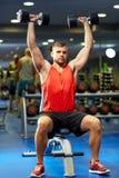 Hombre joven con las pesas de gimnasia que doblan los músculos en gimnasio Fotos de archivo