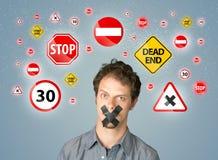 Hombre joven con las señales pegadas de la boca y de tráfico Fotos de archivo