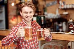 Hombre joven con las tazas de cerveza Imagen de archivo libre de regalías