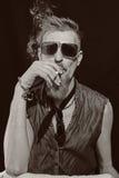 Hombre joven con llevar del cigarrillo gafas de sol Fotografía de archivo