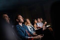 Hombre joven con los amigos en película de observación del pasillo del cine foto de archivo