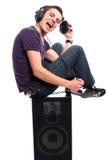 Hombre joven con los auriculares, asentando en un altavoz Foto de archivo libre de regalías