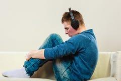 Hombre joven con los auriculares en el sofá Fotos de archivo libres de regalías