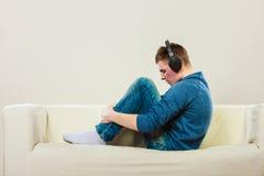 Hombre joven con los auriculares en el sofá Imagen de archivo libre de regalías