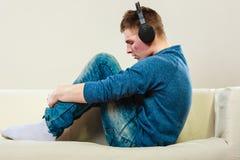 Hombre joven con los auriculares en el sofá Imagen de archivo