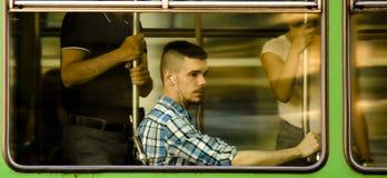 Hombre joven con los auriculares en la sentada de la camisa de tela escocesa mientras que monta adentro Foto de archivo libre de regalías
