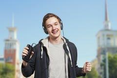 Hombre joven con los auriculares que escucha la música de su teléfono Imagenes de archivo