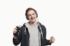 Hombre joven con los auriculares que escucha la música de un smartphone o Fotos de archivo libres de regalías