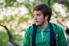 Hombre joven con los auriculares que escucha la música Retrato de la persona en el parque, que está pensando en algo Fotos de archivo libres de regalías