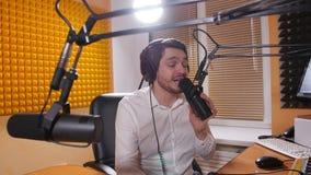 Hombre joven con los auriculares que habla en el mic Concepto en línea de la radio y el hacer un podcast almacen de video