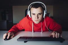 Hombre joven con los auriculares que juegan a los videojuegos en el ordenador El foco del videojugador mira la cámara Foto de archivo libre de regalías