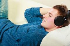 Hombre joven con los auriculares que mienten en el sofá Fotografía de archivo