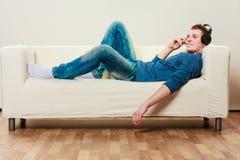 Hombre joven con los auriculares que mienten en el sofá Fotos de archivo libres de regalías