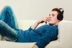 Hombre joven con los auriculares que mienten en el sofá Fotografía de archivo libre de regalías