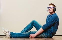 Hombre joven con los auriculares que se sientan en piso Fotografía de archivo libre de regalías
