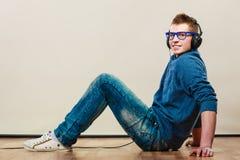 Hombre joven con los auriculares que se sientan en piso Fotografía de archivo