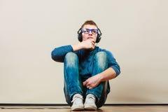 Hombre joven con los auriculares que se sientan en piso Foto de archivo