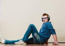 Hombre joven con los auriculares que se sientan en piso Imagenes de archivo