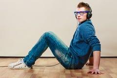 Hombre joven con los auriculares que se sientan en piso Fotos de archivo